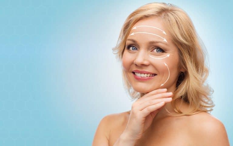 אישה מחייכת עם יד על הפנים לפני ניתוח מתיחת פנים