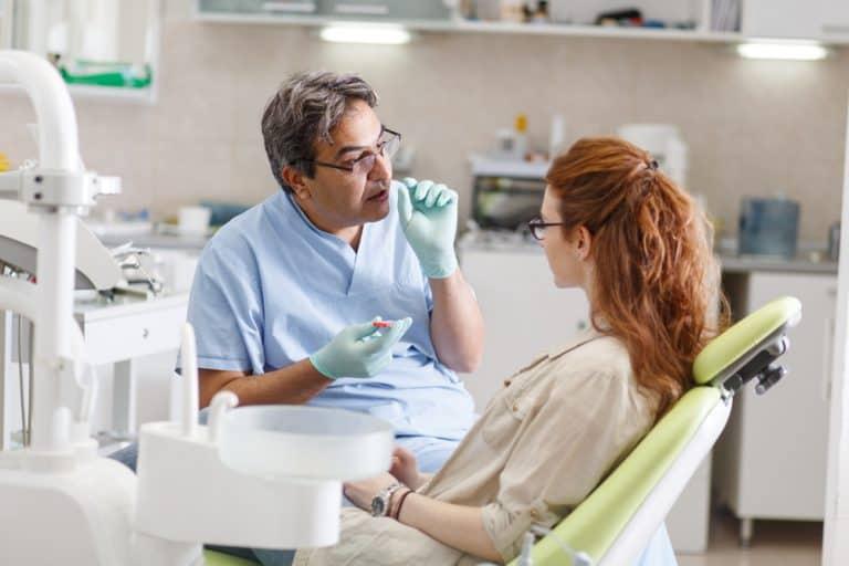 רופא שיניים מסביר למטופלת על אובדן שיניים ומראה לה