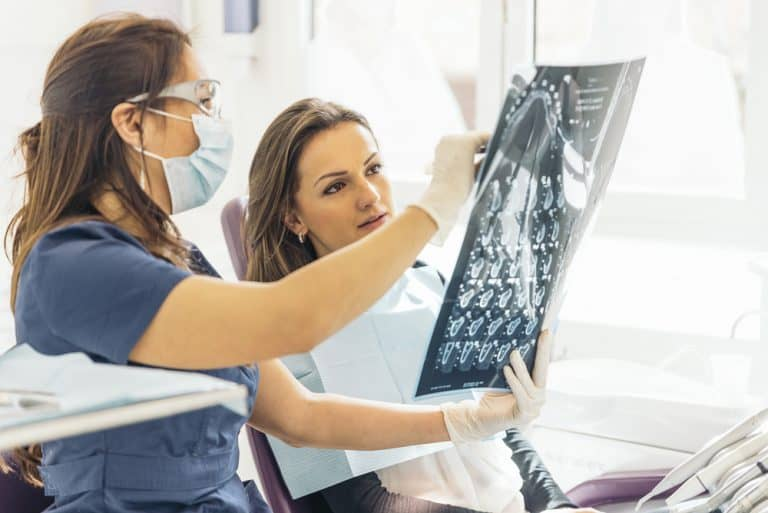 רופאת שיניים מראה למטופלת צילום CT של השיניים שלה