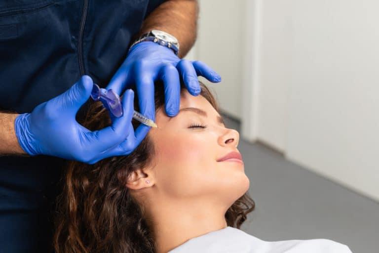 בחורה צעירה באמצע טיפול הזרקה של חומצה היאלורונית