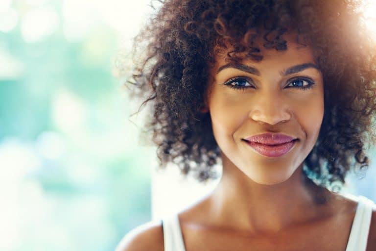 אישה מטולטלת מחייכת באור יום