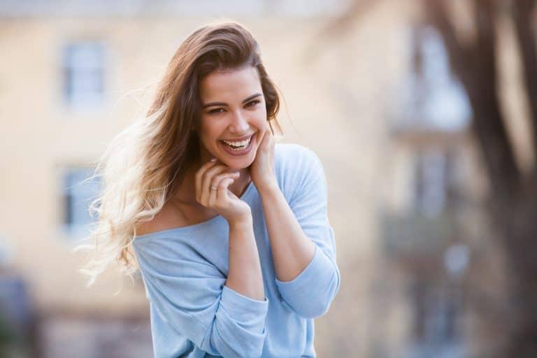 אישה עם חולצה כחולה מחייכת
