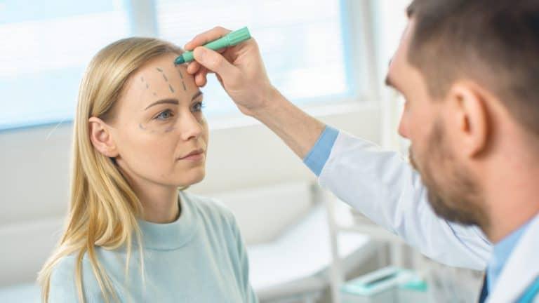 רופא מסרטט את קווי הטיפול על האישה לפני טיפול חוטים