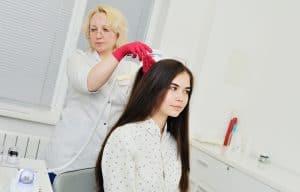 טריקולוגית מבצעת למטופלת אבחון טריקולוגי