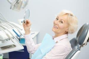 אישה מחייכת לאחר טיפול השתלת שיניים בשיטת אול און פור