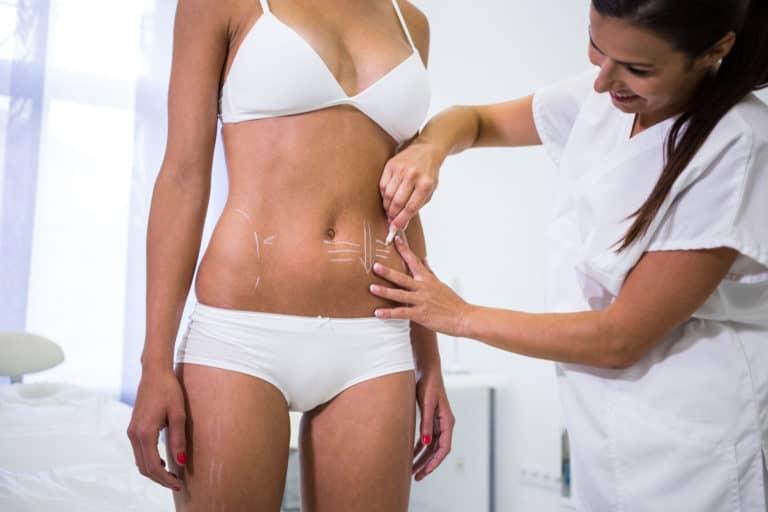 רופאה מודדת בטן של מטופלת