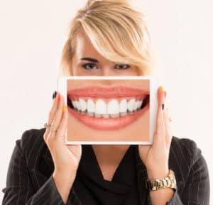 אישה מחזיקה טאבלט המציג את השיניים שלה